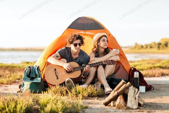 Porträt eines jungen Paares sitzend mit Gitarre in der Nähe von Lagerfeuer