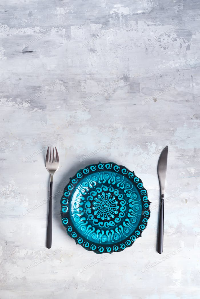 Turkish ceramics decorated blue platewith new luxury black cutlery on stone background, top view