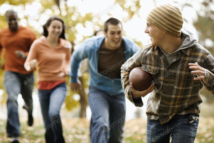 Eine Gruppe von Menschen, Erwachsenen und Jugendlichen, spielen eine Partie Fußball unter den Herbstblättern.