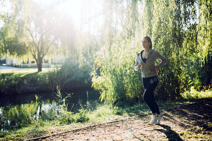 Sporty girl jogging in nature