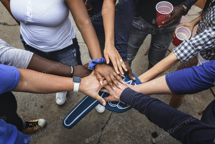 Sports fans in a huddle at a tailgate event