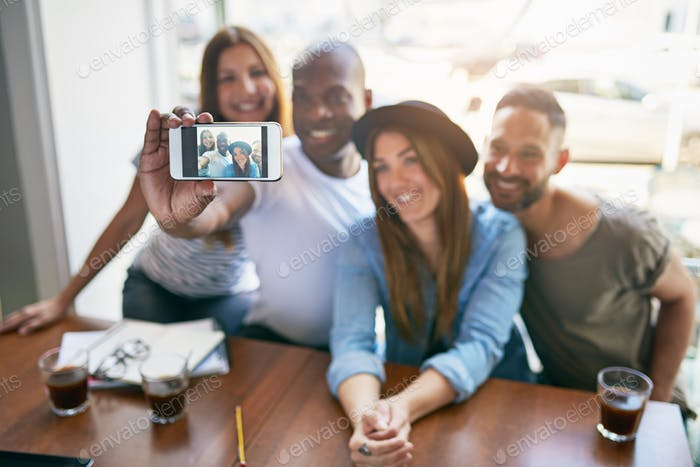 Group of friends taking selfie at table