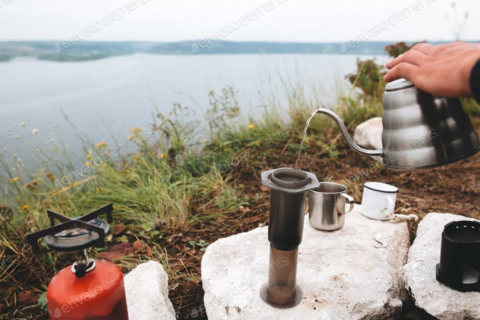 Steel kettle boiling on gas primus, making hot drink at picnic outdoors