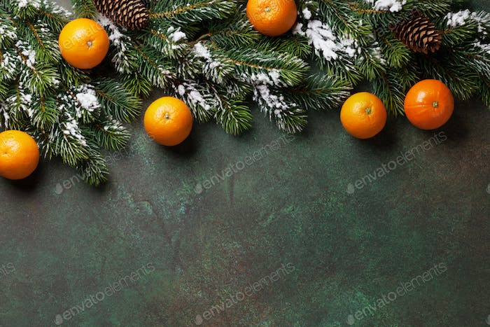 Christmas background with snow fir tree and tangerines