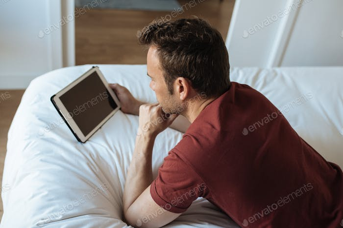 Man lying down on bed with tablet