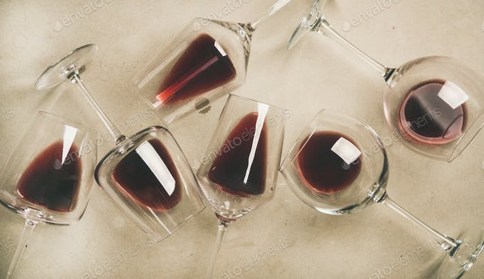 Flat-lay of red wine in glasses over grey concrete background