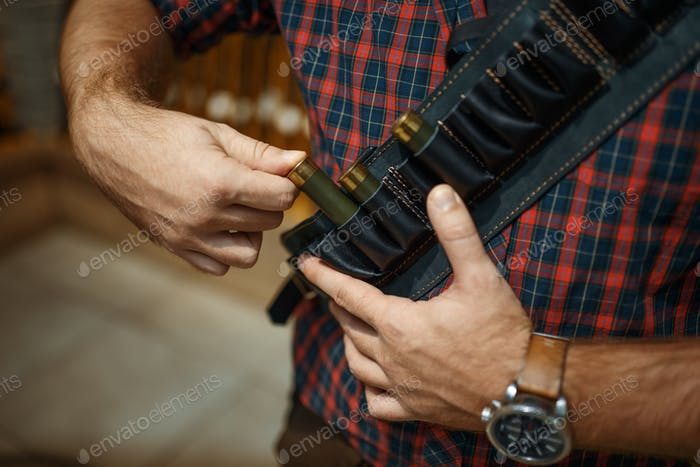 Man in ammo belt, rifles on background, gun shop