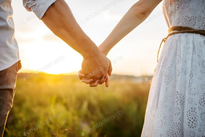 Couple hold hands in green field on sunset