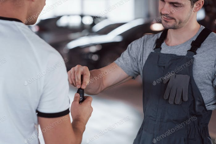 Mechanic gives keys to the owner of the repaired car in the workshop