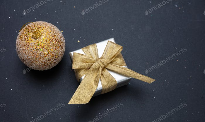 Xmas present and bauble shiny gold color against grey black background