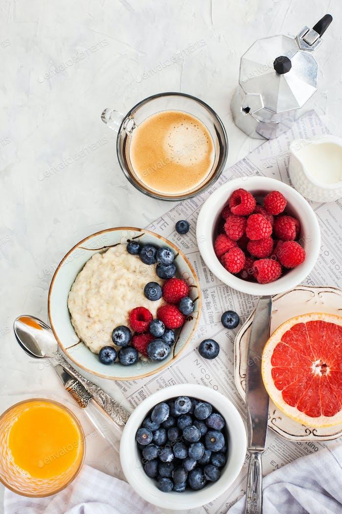 Gesunder Frühstückstisch mit Haferbrei, frischen Beeren und