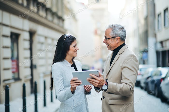 Man and woman business partners with tablet standing outdoors in city, talking.