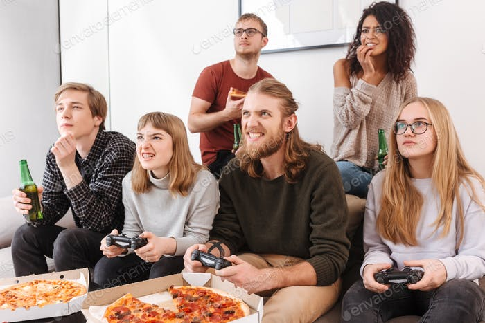 Group of friends on sofa playing video games, eating pizza and drinking beer at home
