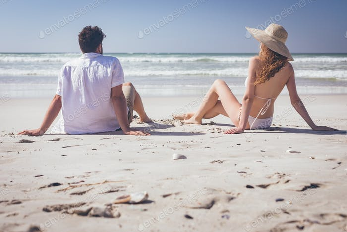 Rear view of young Caucasian couple relaxing at beach on a sunny day. They are looking ocean