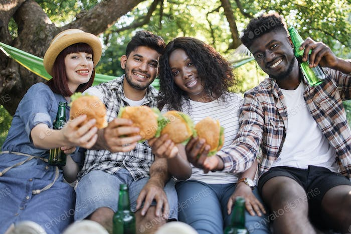 Four friends enjoying picnic with burgers and beer