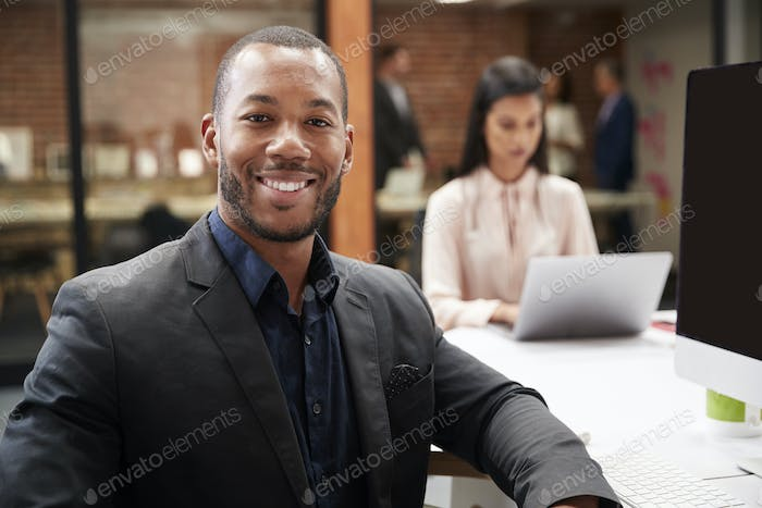 Portrait Of Businessman Working At Desk On Computer In Open Plan Office