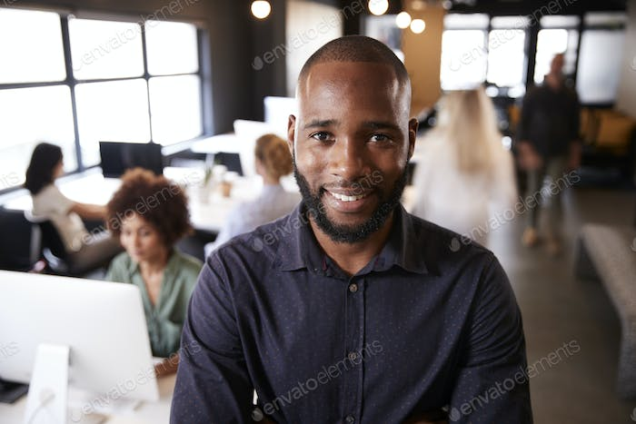 Bearded black male creative standing in a busy casual office, smiling to camera