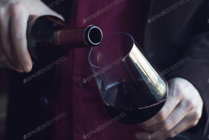 Mann gießt Rotwein in ein Glas