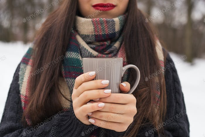 Beautiful happy smiling woman with a cup in the winter on the street