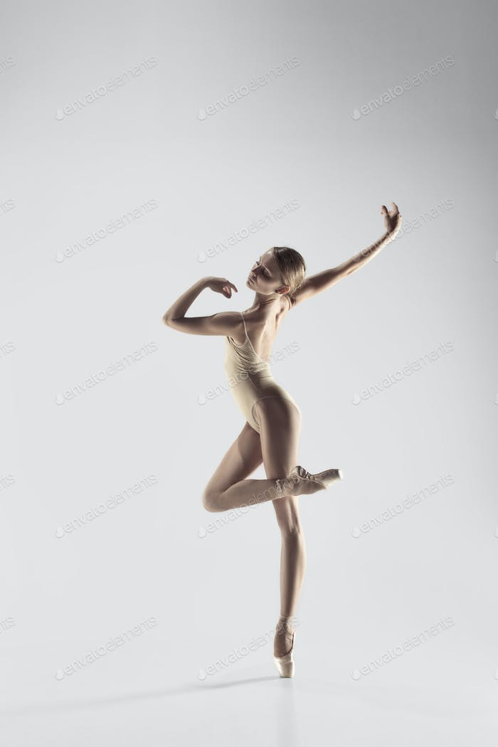 Ballerina. Young graceful female ballet dancer dancing at studio. Beauty of classic ballet.