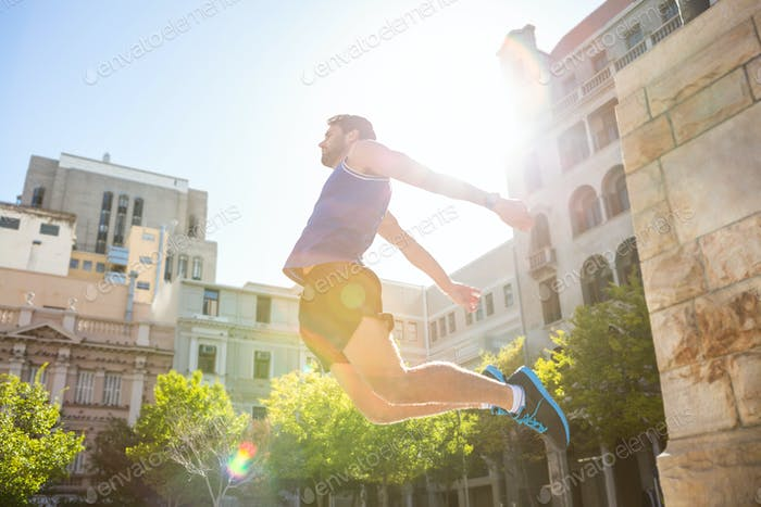 Handsome athlete jumping in the city