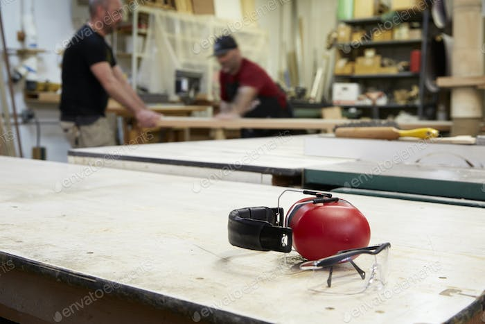 Close up of headphones and safety goggles on workshop table