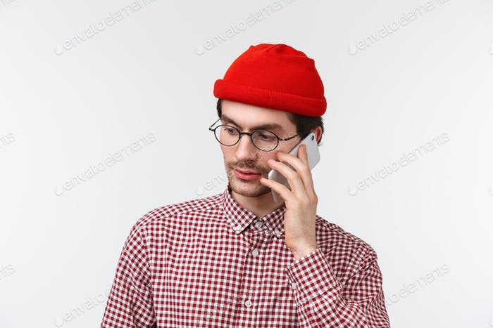 Close-up portrait of serious-looking young man in red beanie and glasses calling someone on mobile