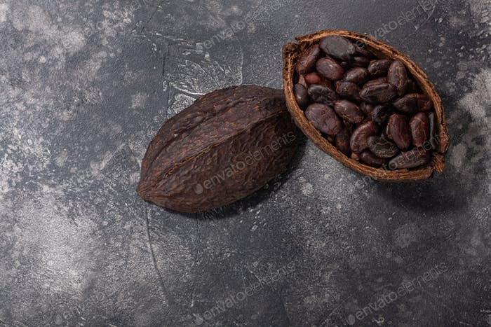 Split fermented cocoa pod with shelled cacao beans atop dark grey backdrop,  top view
