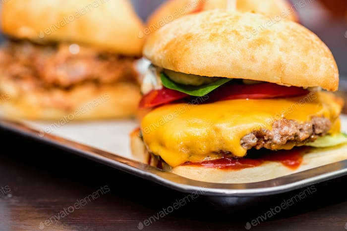 Close up three tasty burgers with different filling served on tray