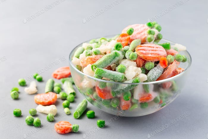 Glass bowl with frozen vegetables on table