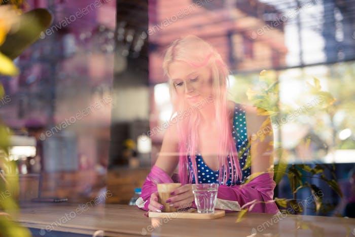 jóvenes hermosa rubia mujer bebiendo café en el café tienda