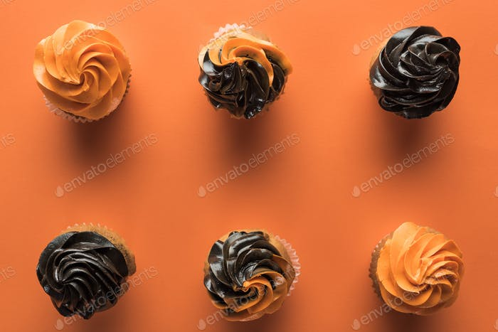 Top View of Delicious Halloween Cupcakes on Orange Background With Copy Space