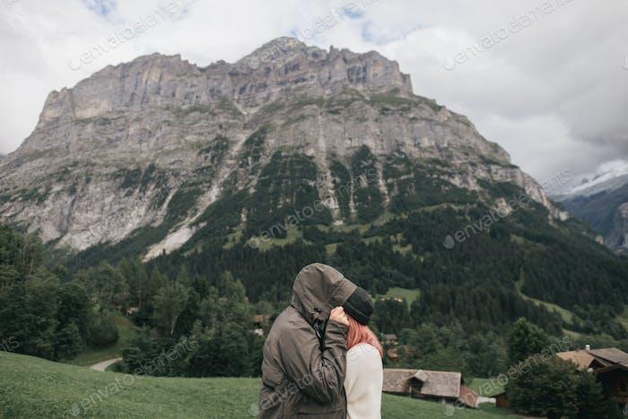 Seitenansicht junges Paar in der Liebe umarmt und Berglandschaft dahinter, Bern, Schweiz