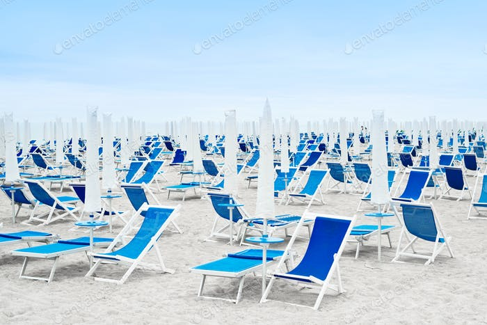 Beach umbrellas and blue deckchairs