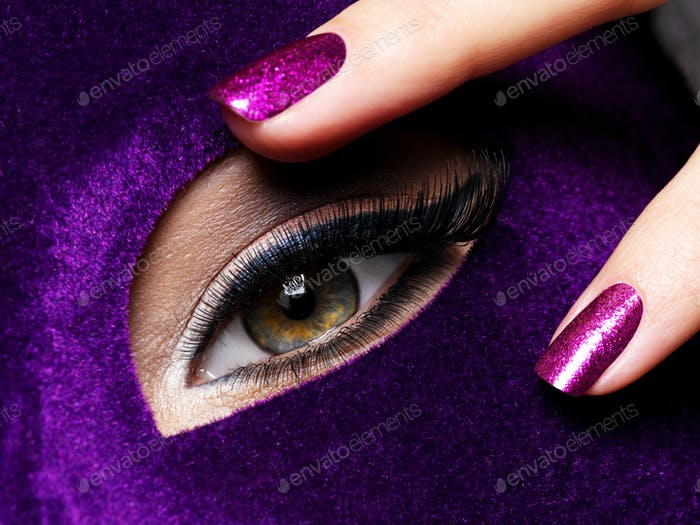 Woman's fingers with purple nails about eye. Macro photo