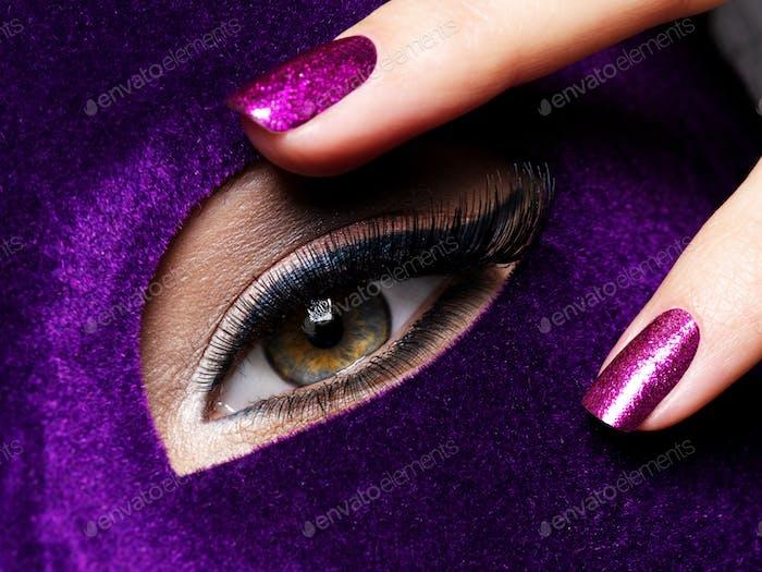 Die Finger der Frau mit lila Nägeln über das Auge. Makrofoto