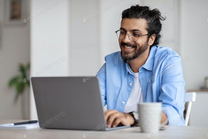 Lächelnder indischer Schriftsteller mit Laptop-Computer, Sitzen am Schreibtisch In Heimbüro
