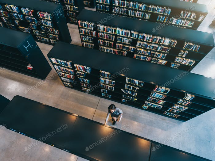Junge Frau auf der Suche nach einem Buch im Regal