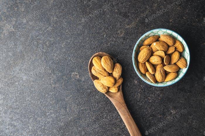 Nueces de  almendras secas en cuchara y tazón.