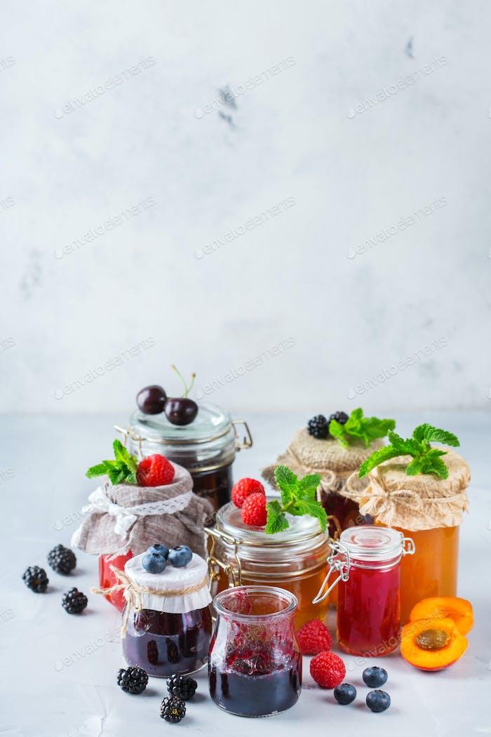 Auswahl an saisonalen Beeren und Obstmarmeladen in Gläsern