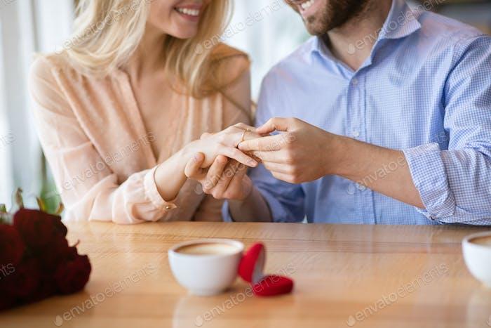 Abgeschnittene Ansicht eines tausendjährigen Mannes, der die Hand seiner Verlobten mit Diamant-Verlobungsring im Café hält