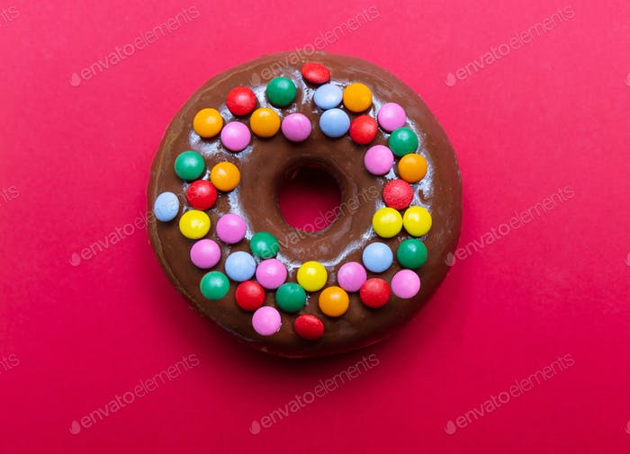 Chocolate doughnut with colorful decoration on red color background, top view