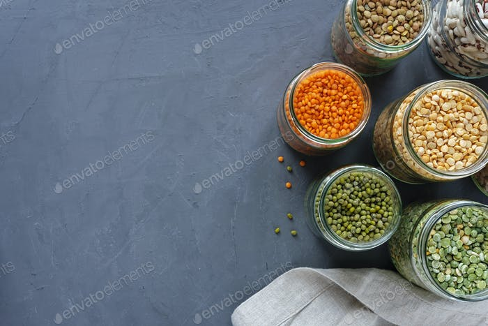 Dried legumes in storage jars on mottled blue