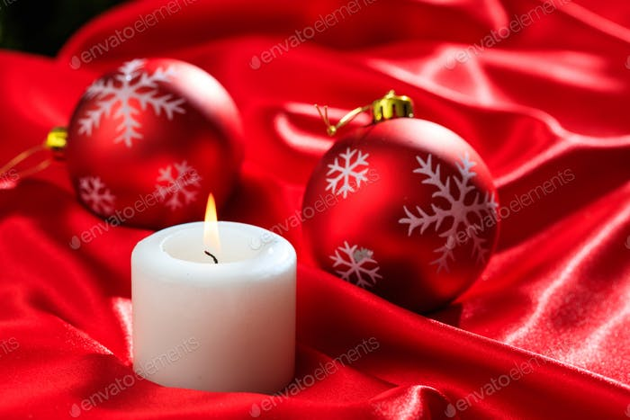 Christmas balls and candle on red satin background