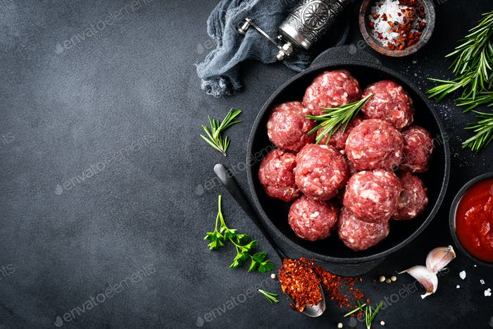 Fresh raw beef meatballs with spices and tomato sauce