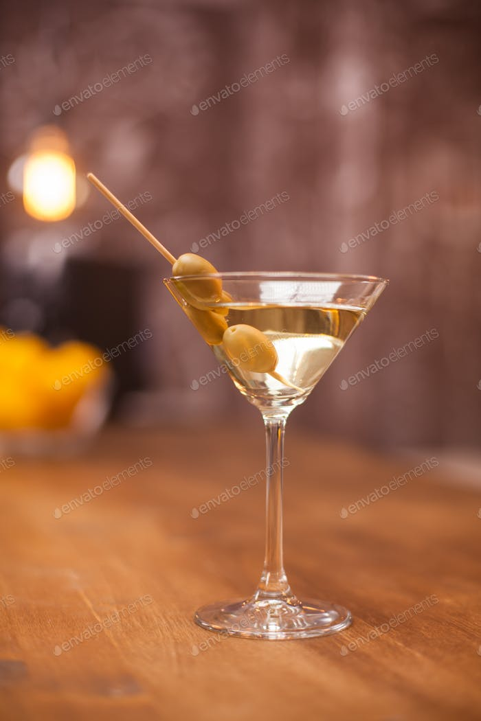 Transparent glass filled up with dry white martini on a counter bar