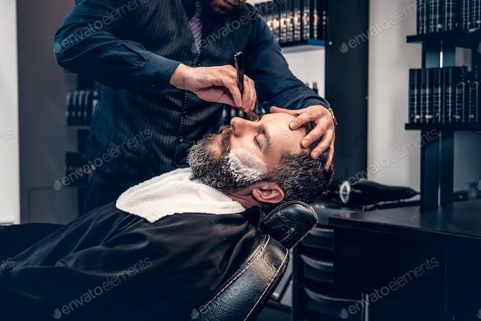 Крупным планом портрет парикмахера бритья бородатый мужчина с острой бритвой в салоне.