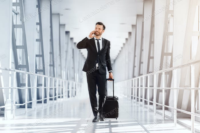 Wealthy handsome entrepreneur with suitcase walking by airport