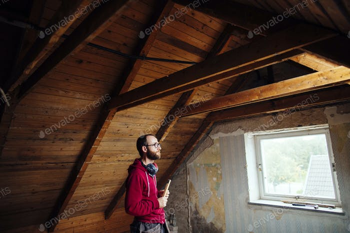 Side view of man inspecting attic under renovation
