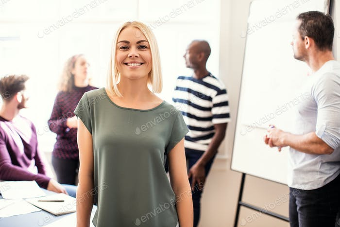 Smiling young designer standing in an office after a meeting